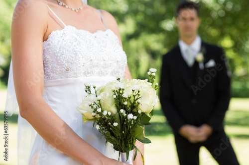 Bride holding bouquet with groom in background
