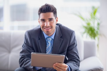Businessman sitting on sofa using his tablet smiling at camera