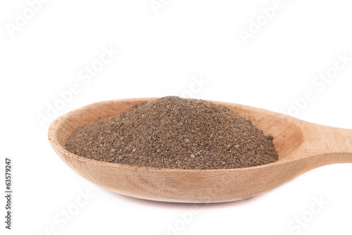 Wooden spoon with powdered black pepper.