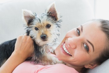 Happy woman cuddling her yorkshire terrier on the couch