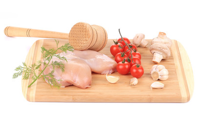 Raw chicken breast with tomatoes and mushrooms.