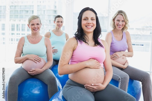 Smiling pregnant women sitting on exercise balls