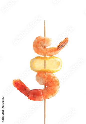 Grilled shrimps with lemon on skewer.
