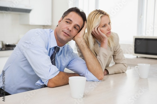 Business couple not talking after an argument in kitchen