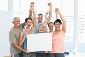 Portrait of happy fit people holding blank board