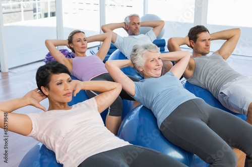 Sporty people stretching on exercise balls