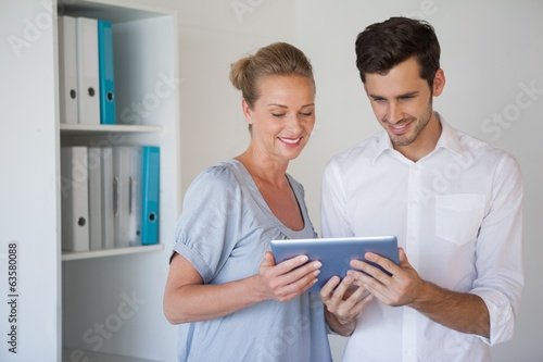 Casual business team using tablet together