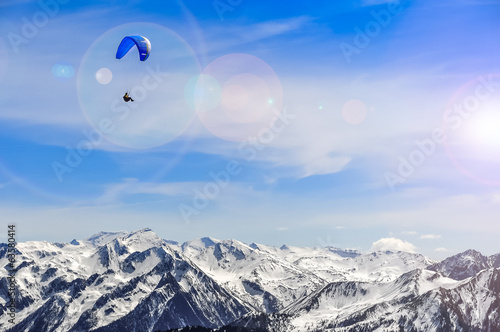 Winter mountains landscape and man paragliding