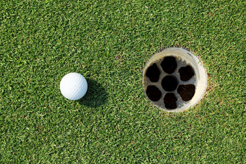 golf ball near the hole on green grass