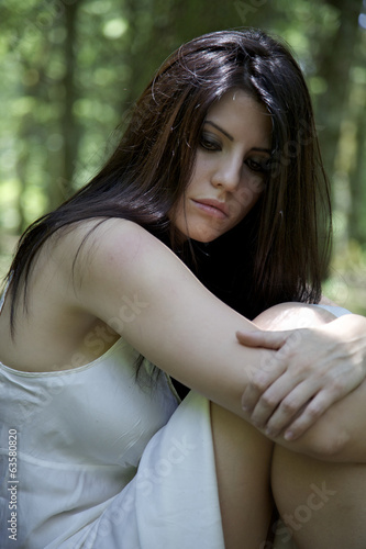Sad woman thinking in forest
