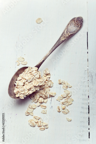 Oat flakes in an old spoon on wooden table, toned photo