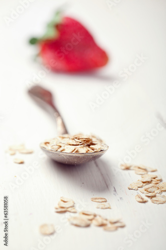 Oat flakes in an old spoon and a strawberry on wooden table