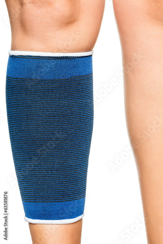 Young woman with an elastic band on her leg isolated on white