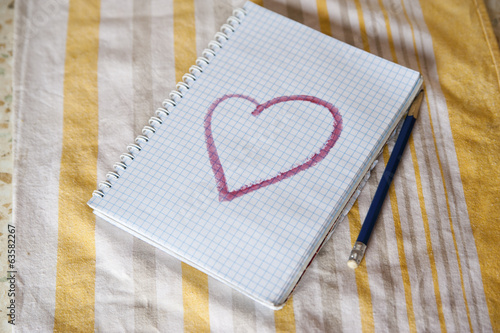 notebooke with pictured heart and pencil on a striped towel