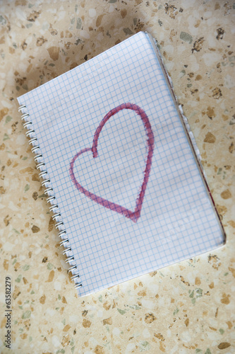 notebooke with pictured heart on a table