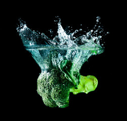 Green broccoli falling in water on white with air bubbles