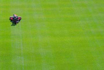 Stadium workers trim football field grass.