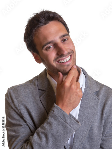 Latin businessman in grey laughing at camera