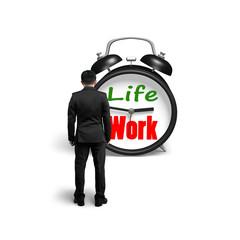 Man facing alarm clock with life and work face
