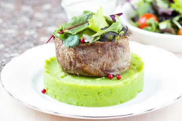 Grilled beef steak, green mashed potatoes with peas, herbs