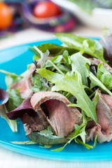 Green salad with grilled beef steak medium rare, mix lettuce