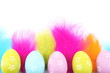 Easter eggs and decorative feathers, isolated on white