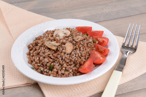 Boiled buckwheat on plate on table close-up