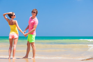 Couple in bright clothes holding hands on tropical beach.
