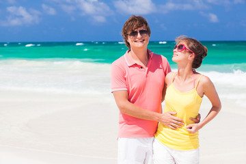 Couple in bright clothes hugging on tropical beach