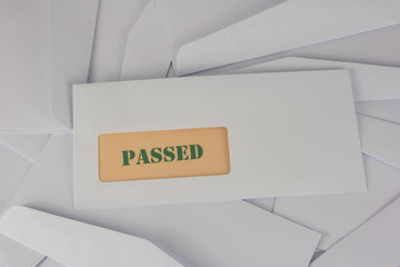 passed announcement from white envelope on heap of envelopes
