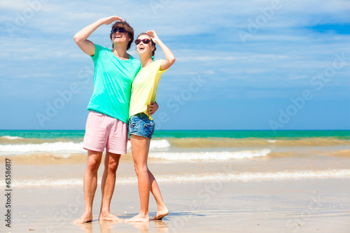 Portrait of happy young couple in sunglasses on tropical beach