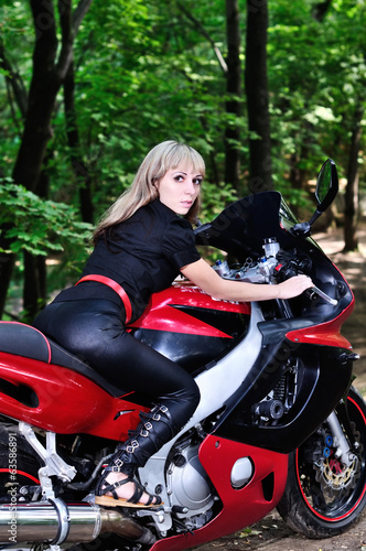 The girl on a sports bike in the woods is looking back