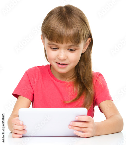 Young cheerful girl is using tablet
