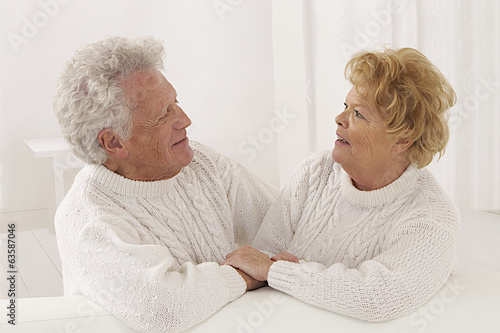 happy senior couple in white looking and smiling