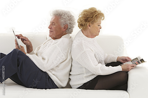 Senior couple seated back to back  playing