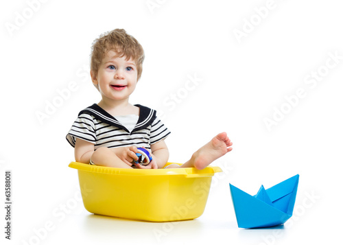 sailor boy sitting inside bathtub