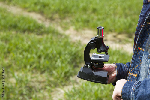 Child holds a microscope in hand standing in the field