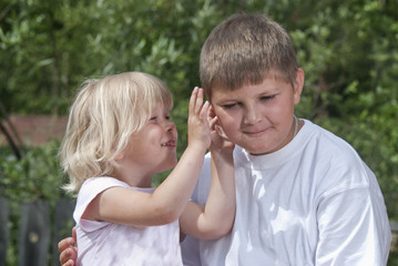 Children. The girl whispers a secret on an ear to brother