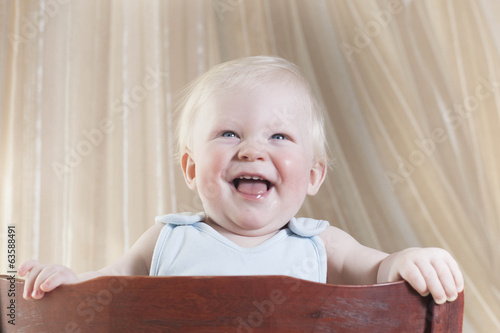 The little boy of 8 months costs on a chair and talks loudly