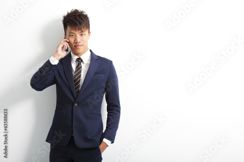 smiling young man using smartphone to conversation
