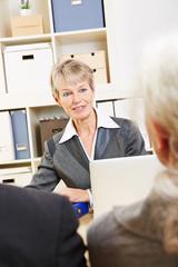 Frau in Bank berät Kunden