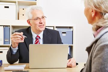Berater macht mit Kundin Finanzplanung
