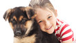little girl tenderly embraces a German Shepherd puppy