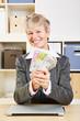 Lachende Seniorin mit Fächer aus Geldscheinen