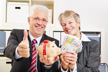 Senioren mit Sparschwein und Geld halten Daumen hoch