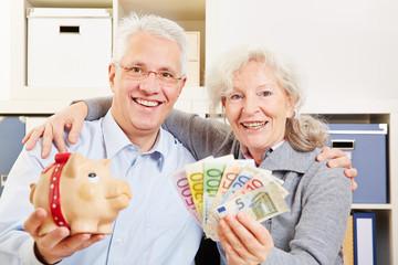 Lachendes Paar Senioren mit Geld und Sparschwein