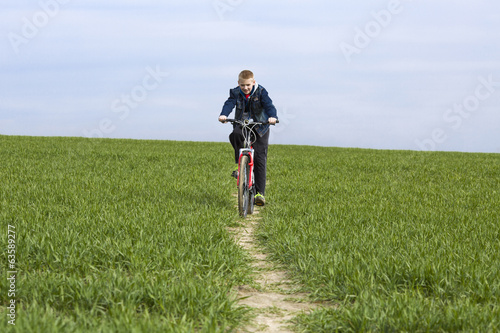 Boy goes by bicycle on a green field