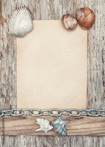 Old paper, seashells and metal chain on the old wood