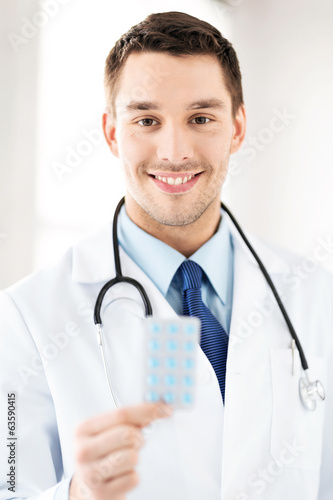 young male doctor with pack of pills