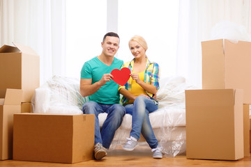 smiling couple with red heart on sofa in new home